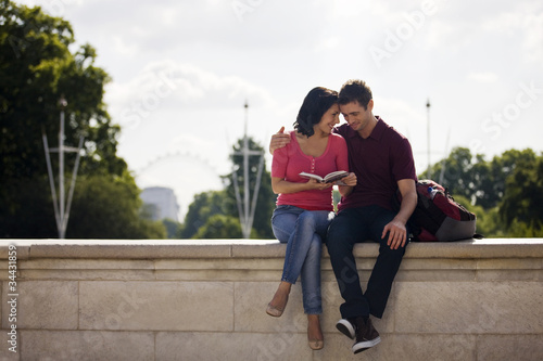 A young couple sitting on a wall, reading a guidebook