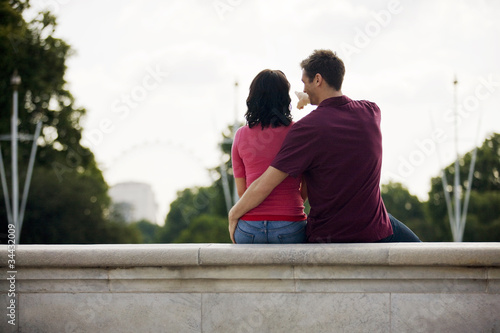 A young couple sitting on a wall