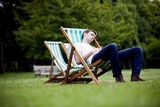 A young man relaxing on a deckchair in St James Park