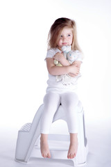 Junges Mädchen kuschelt mit Teddybär und blickt fern, hoch
