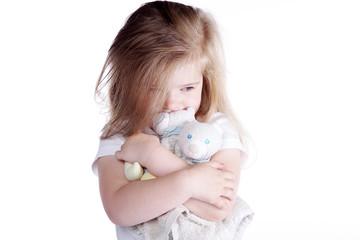 Junges Mädchen kuschelt mit Teddybär, quer