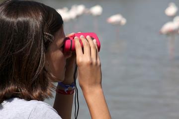 adolescente osserva fenicotteri con binocolo