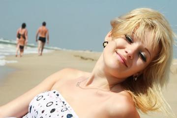 a portrait of the blond girl on a sea beach