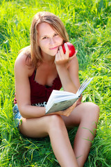 Young woman sitting in grass reading book an apple in his hand