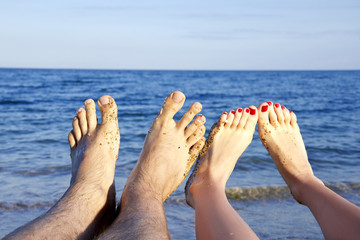 Feet of the man and young woman on the sea background