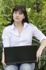 Junge attraktive Frau mit Laptop im Garten