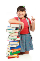 happy young girl laughing with a pile of books beside her