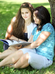 beautiful mother and daughter reading fairy book in summer park