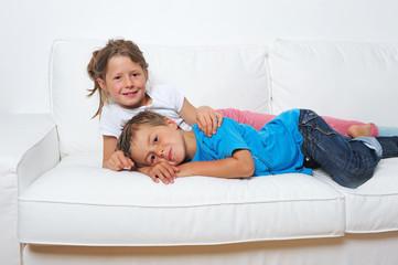 Zwei Kinder liegen auf dem Sofa