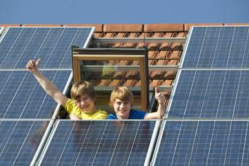 Kinder in Dachfenster mit Solarplatten