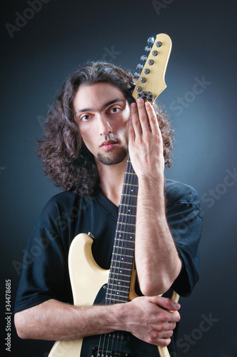 Guitar player against the dark background