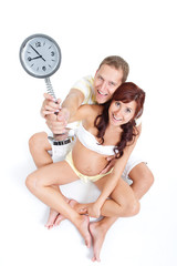 Pregnant woman with husband, holding a clock showing 9th month,