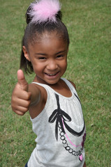 Little Girl in Grass Giving Thumbs Up