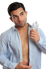 Man with bottle of cologne while dressing