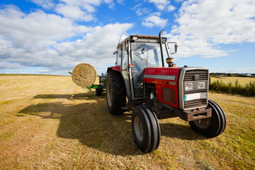 tractor collecting a roll of haystack in the field