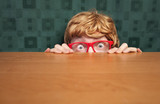 Fototapety Scared nerd hiding behind a desk