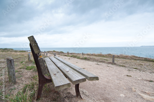 Wooden bench facing the sea on a cloudy day