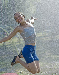Young pretty girl jumps joyfully under the rain drops