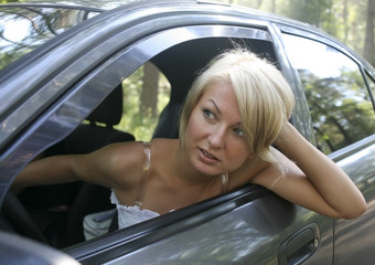 Closup portrait of young pretty blonde driving the car