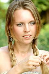 Молодая женщина заплетает (расплетает) косы
