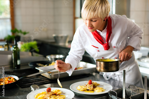 Female chef in a restaurant or hotel kitchen cooking