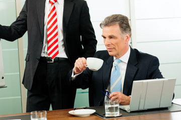 Senior Manager or boss in meeting drinking coffee