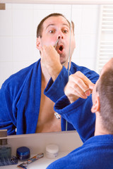 man cuts hair in the nose