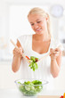 Portrait of a blonde woman mixing a salad