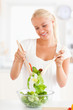Portrait of a smiling woman mixing a salad