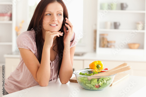 Woman telephoning in kitchen