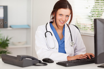 Smiling female doctor typing
