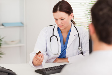 Female doctor looking at pills