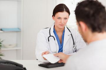 Serious doctor giving patient prescription
