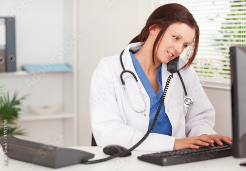 Female doctor telephoning and typing