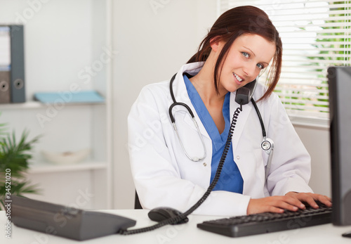 Female doctor is telephoning and typing