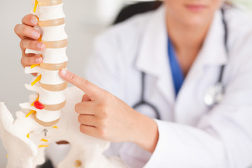 Doctor pointing at bone in spine