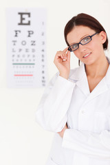 Female optician with glasses and eye test