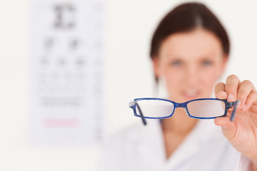 Blurred optician showing glasses
