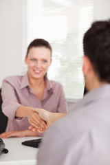 Businesswoman shakes hands with a customer