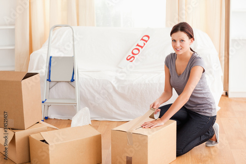 Female preparing cardboard box for transport