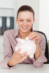 Businesswoman putting money in piggy bank