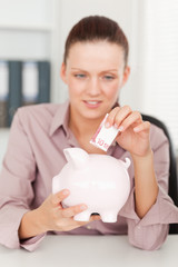 A businesswoman inserting money in piggy bank