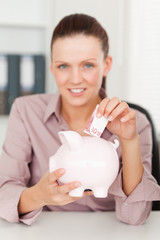 Businesswoman putting money into piggy bank