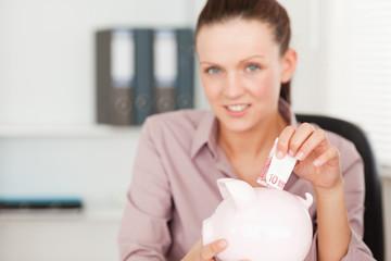 Businesswoman putting 10 euro in piggy bank