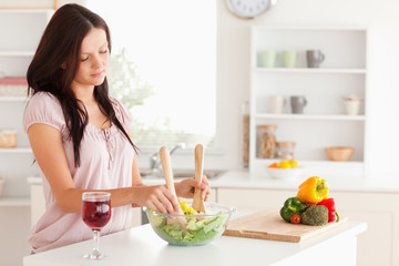 Young woman mixing a salad