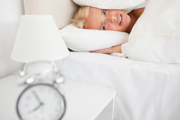 Tired woman hidding her head in a pillow while the alarmclock is