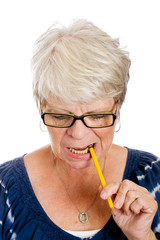 Elderly woman biting a pencil while thinking