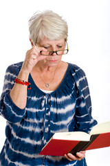Mature woman peering over glasses reading book.
