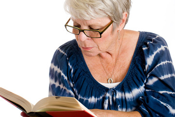 mature, gray haired woman reading a book with glasses