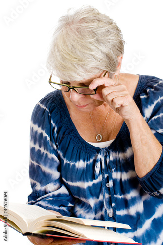 mature woman squinting through glasses to read a book